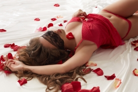 Curvy slim girl with blindfold posing in bed